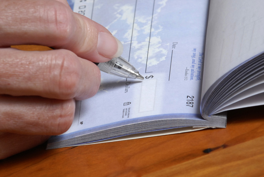 Image of hand writing a check